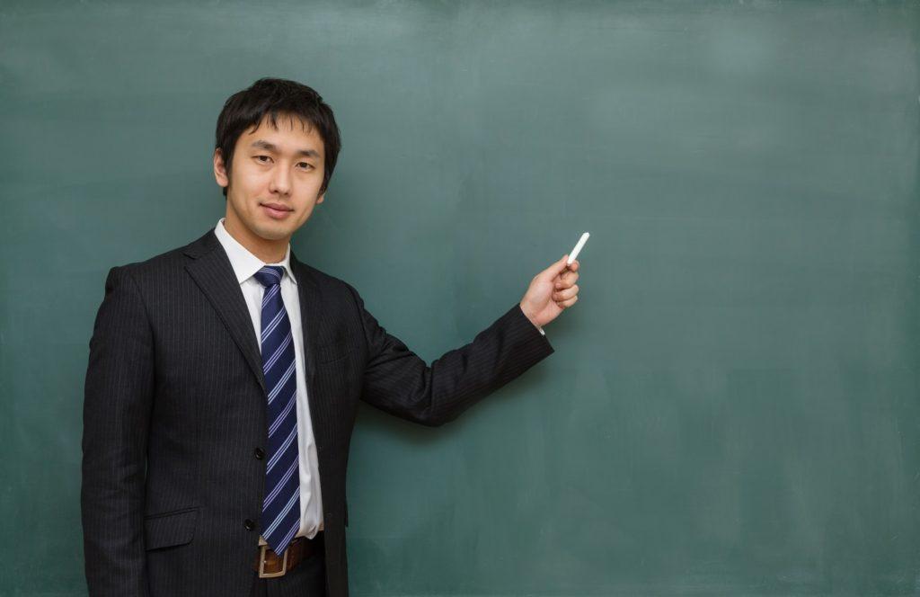 黒板で解説する男性